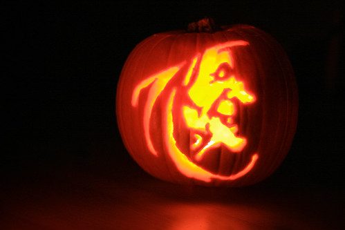 A witch carving on a pumpkin