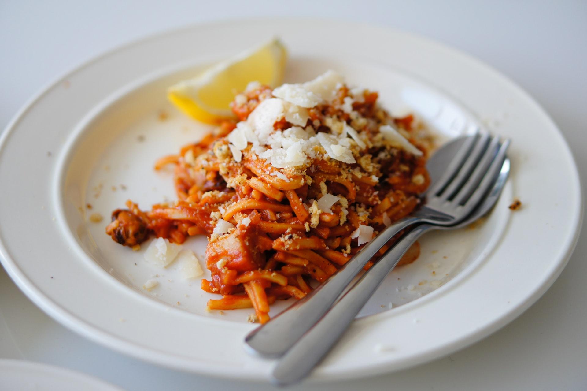 Plate of half eaten spaghettis with a lemon wedge