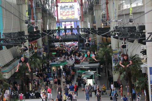 People ziplining over crowd in commercial corridor