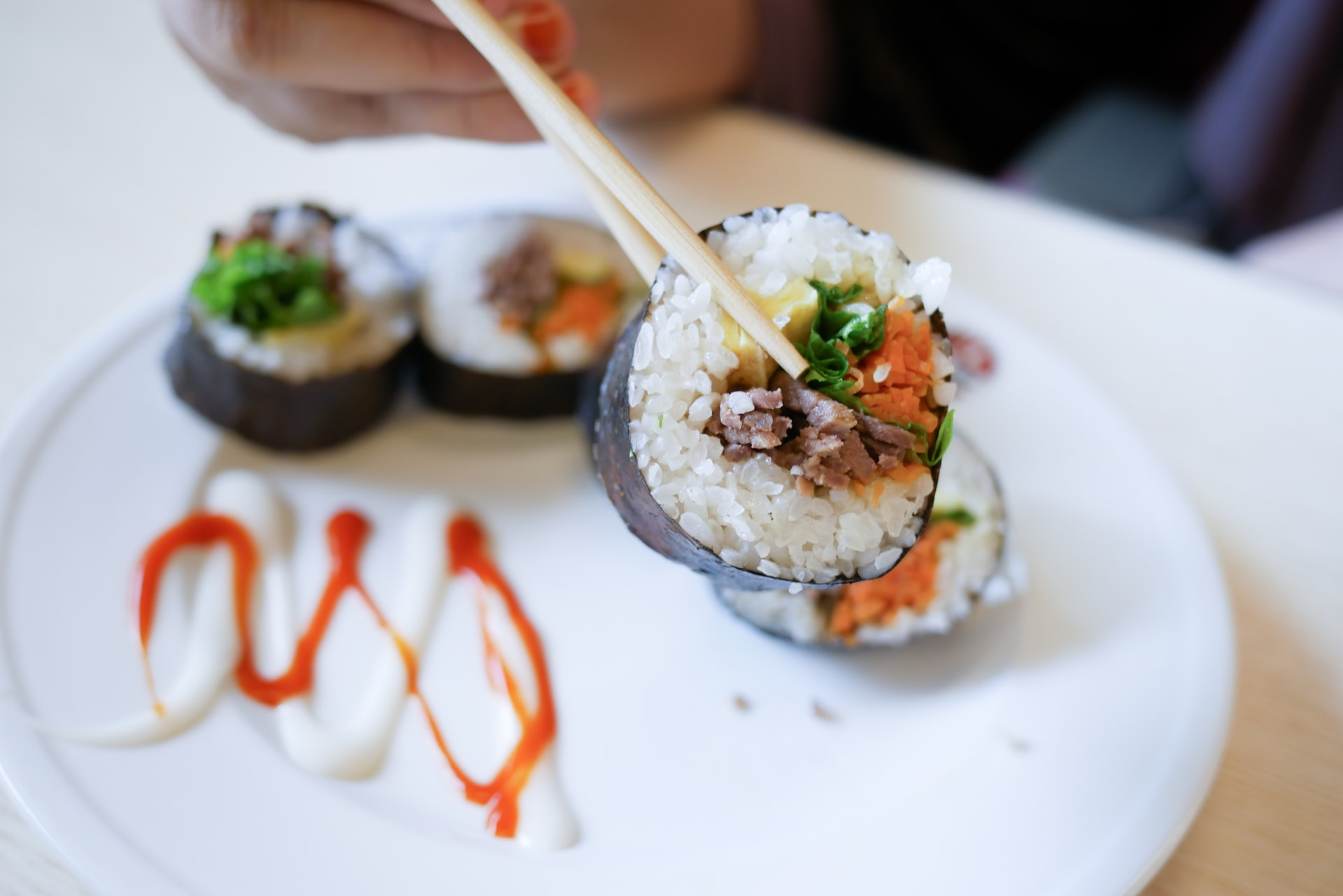 A roll of sushi being held in chopsticks over a plate of other sushi rolls