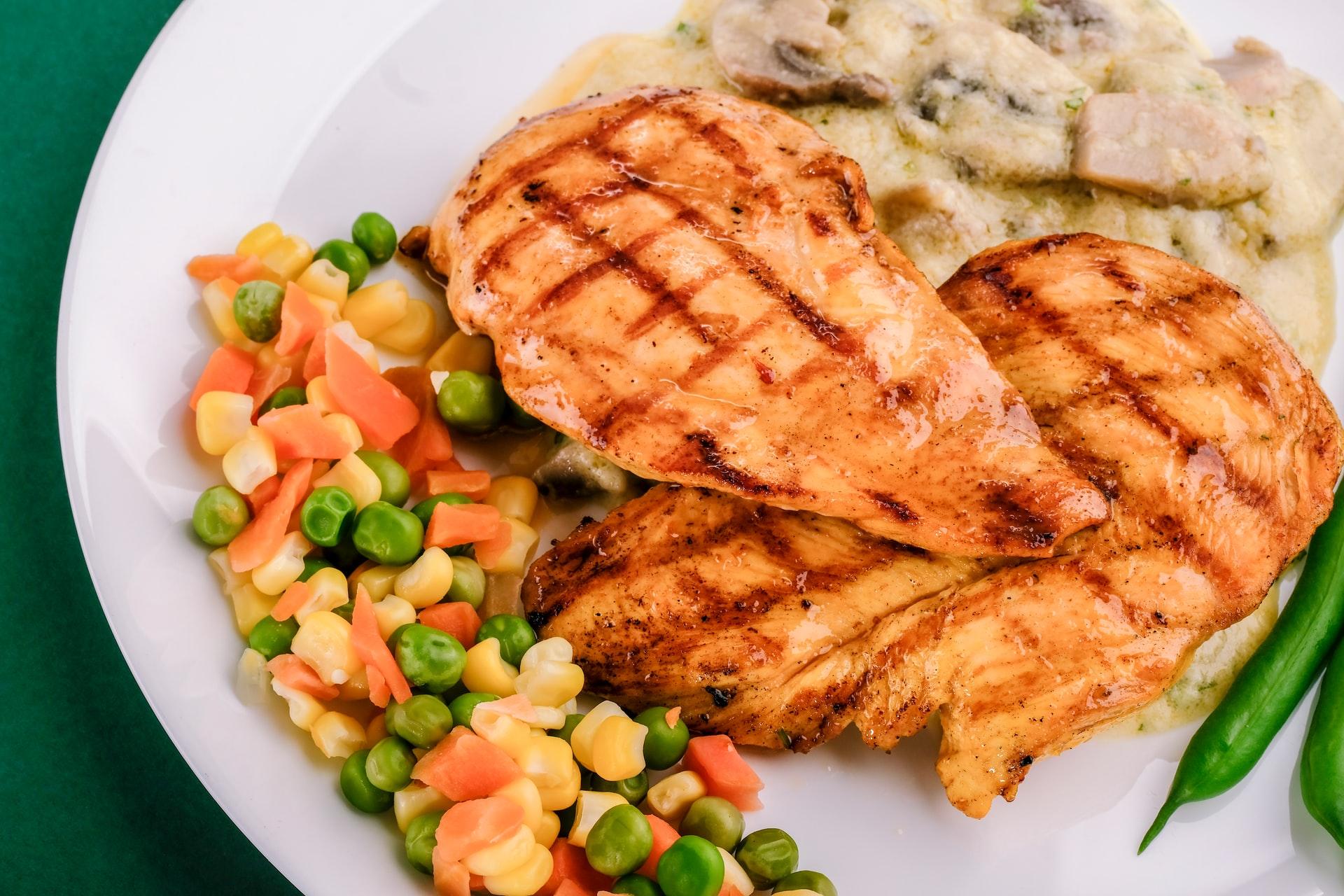 Overhead on plate of grilled chicked with steamed vegetables