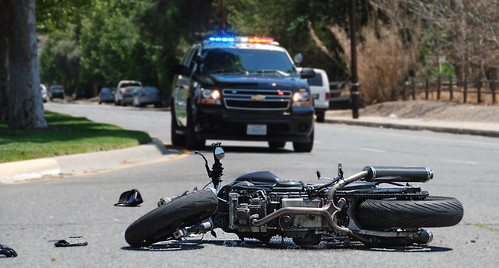 Motorcycle that crashed with a cop car in the background