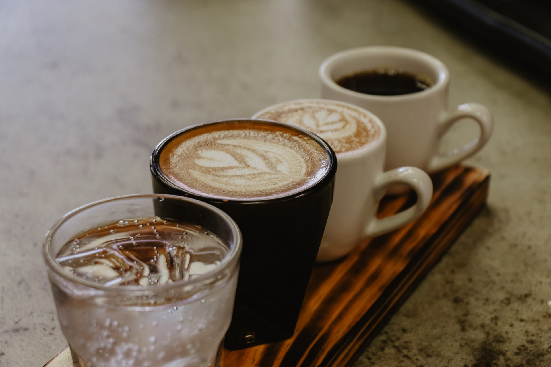 Wooden plank with a glass of water, 2 lattes with foam art, and one cup of black coffee
