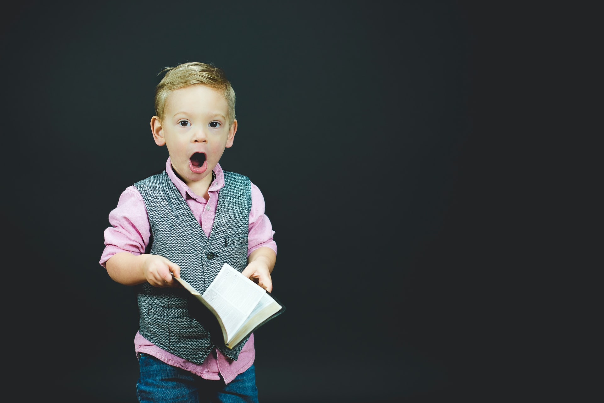 Boy in pink shirt with gray vest reacts with shock to open book in his hands