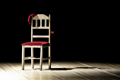 Chair with a red seat on a theatre stage in a spotlight