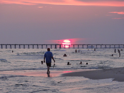 Man with fishing pole on crowded beach at sunset