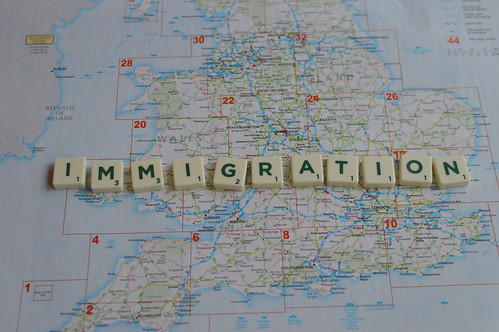 Immigration spelled out in scrable letters over a map