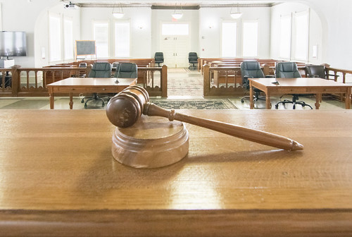 a legal court room taken from the perspective of the judge with the gavel in the foreground