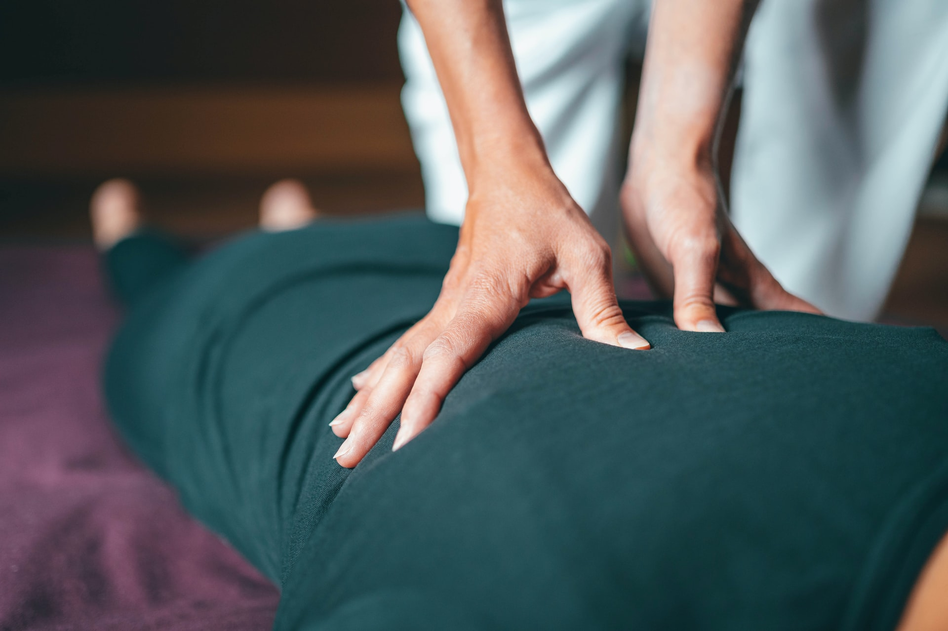 Spa employee giving client a massage on their upper back