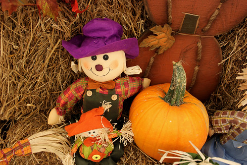 Small scarecrow doll sitting on hay with pumpkins