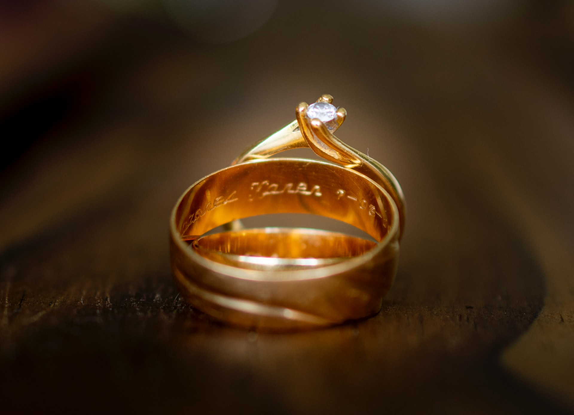 Golden ring with inscription on inside and diamond embedded in it