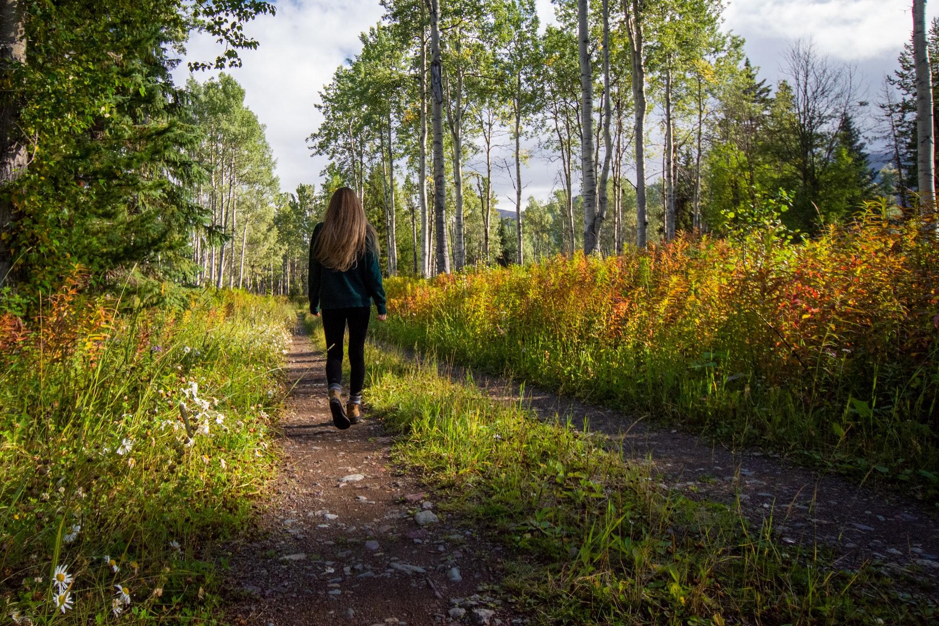 Girl walking through vibrant nature path